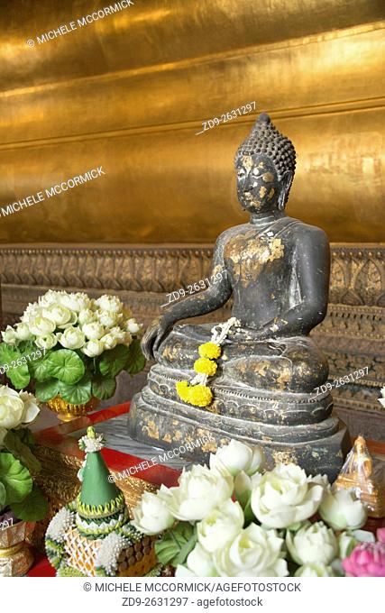 Floral offerings are made to a small Buddha at Wat Pho Temple in Bangkok