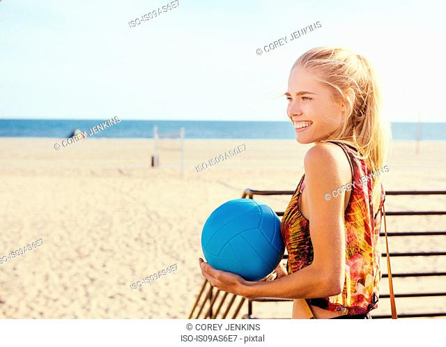 Young woman standing by beach, holding ball