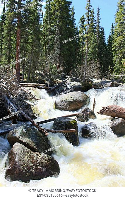 The rushing water of Copeland Falls flowing over boulders in the Rocky Mountain National Park, on the Wild Basin Trail, in Colorado, USA