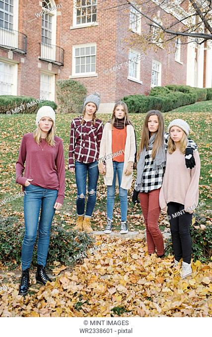 A group of five teenage girls outdoors in woolly hats and scarves