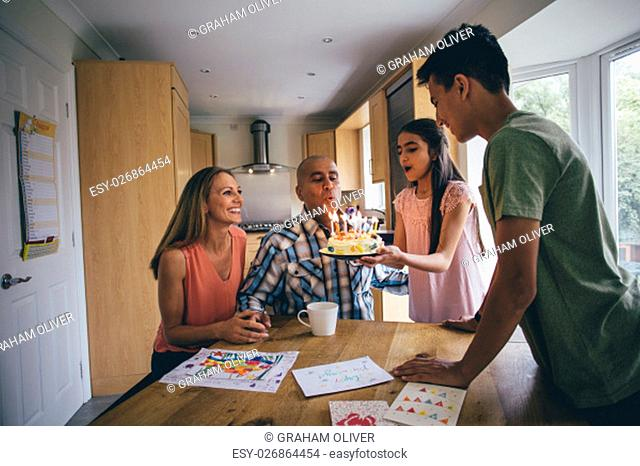 Family of four celebrating the dads birthday. His daughter is holding a cake they have made and is helping him blow out the candles