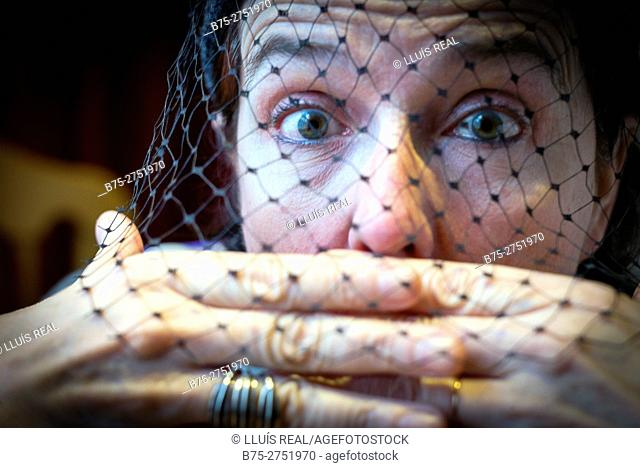 Middle-aged woman with a veil in front of face, with both hands over her mouth and surprised look