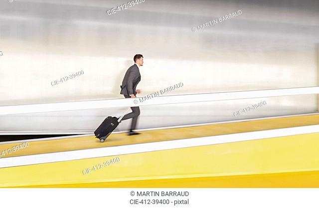 Businessman running, pulling suitcase up airport ramp