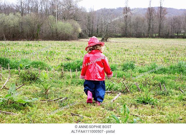 Little girl wearing rain gear playing in field