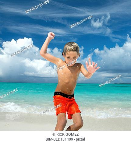 Hispanic boy playing on beach