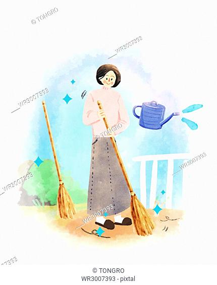 Smiling housewife with a broom sweeping