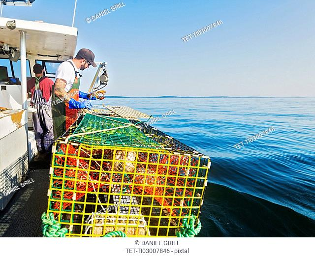 Two fishermen working on boat