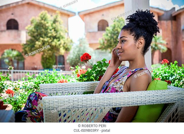 Young woman relaxing on apartment patio talking on smartphone, Costa Rei, Sardinia, Italy