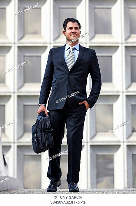 Full length front view of business man, hand in pocket, carrying briefcase
