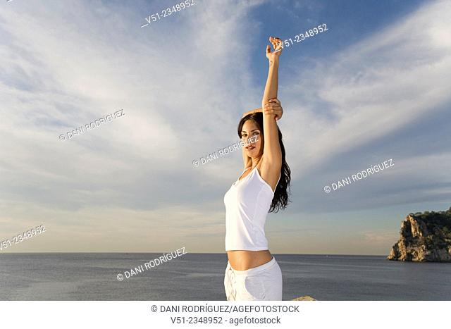 Portrait of a brunette woman breathing fresh air by the sea smiling at camera