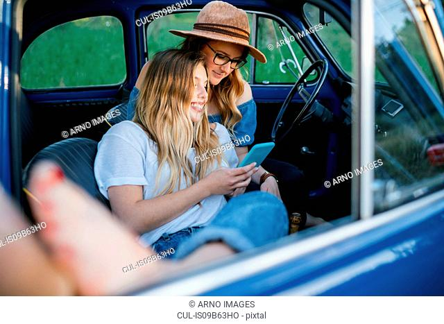Friends sitting in car using digital tablet, Firenze, Toscana, Italy, Europe