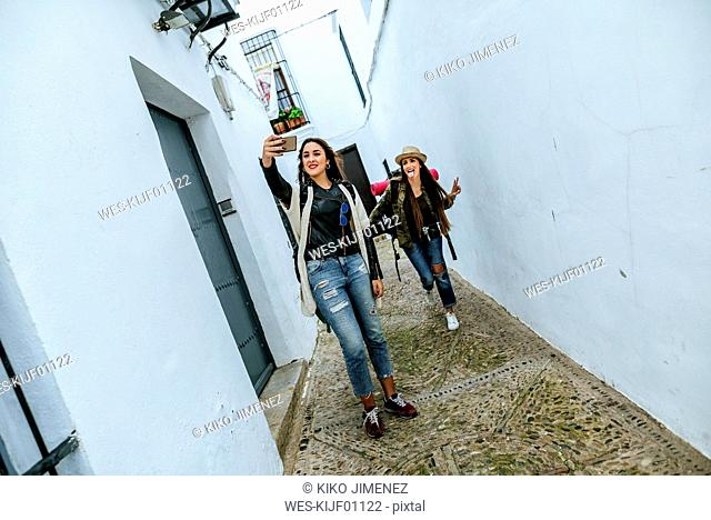 Two young women on a trip walking in a town taking a selfie