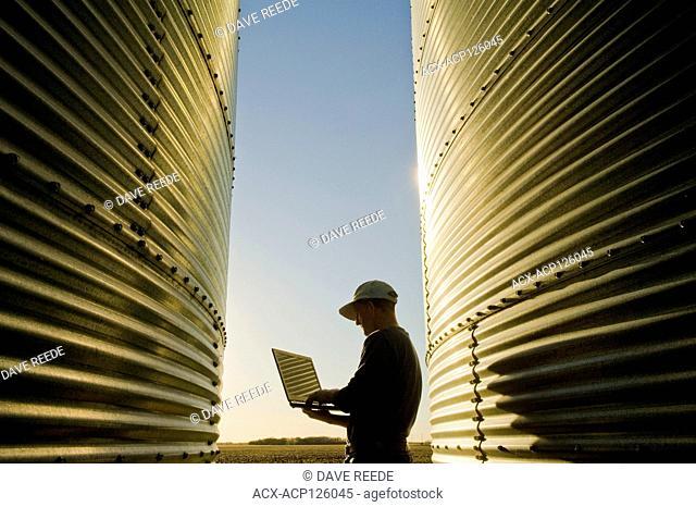 a farmer using a computer next to his on farm grain storage bins, near Dugald, Manitoba