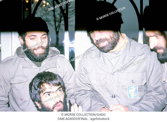 Scene of four bearded men wearing military uniforms engaged in discussion, in a hotel in Iran, March, 1983. Extensive damage on original photo. ()