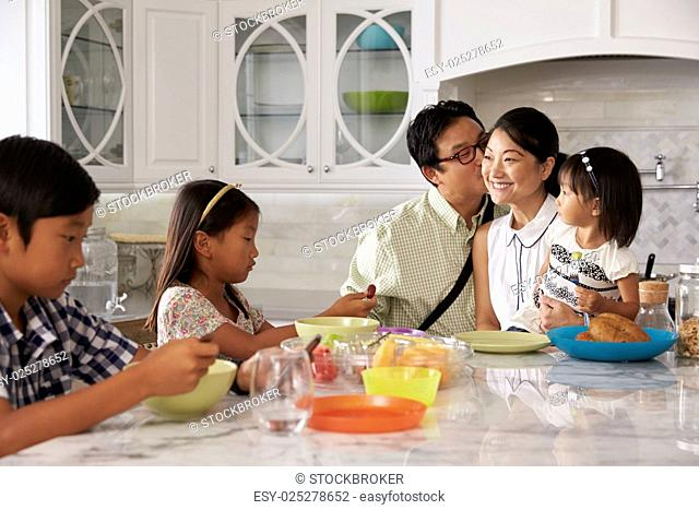 Father Leaving For Work After Family Breakfast In Kitchen