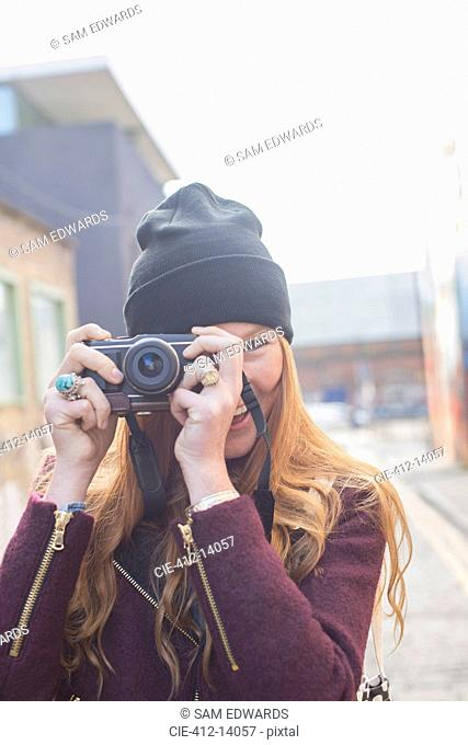 Woman using camera on city street