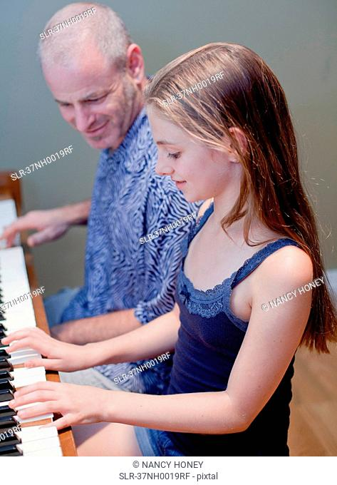 Father and daughter playing piano
