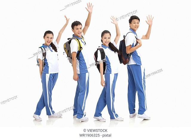 High school students carrying bags waved