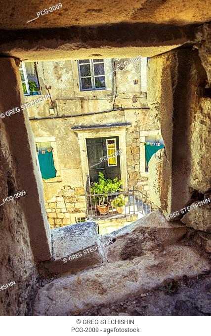 A home and front door in the old city of Dubrovnik framed by a window arch in the city's outer protective wall. UNESCO world heritage site
