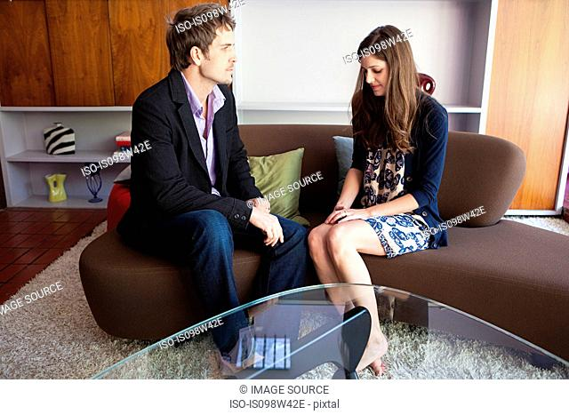 Couple sitting on sofa having serious discussion