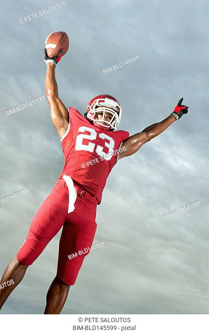African American football player with arms raised holding football