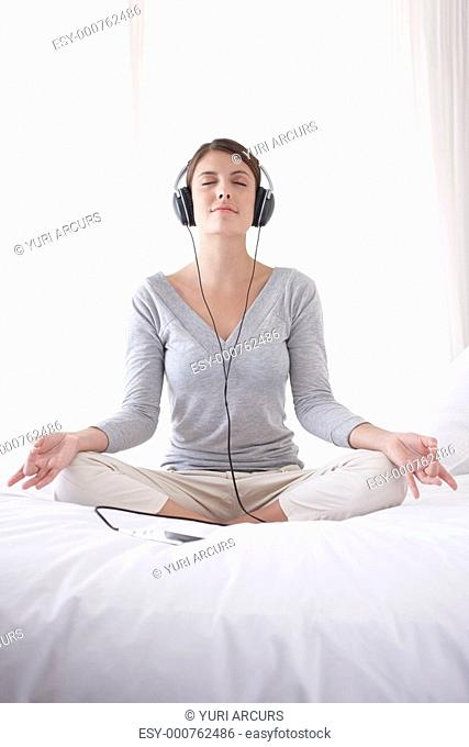 Pretty young woman meditating in lotus position while listening to music