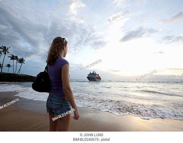 Mixed Race woman standing on beach watching cruise ship