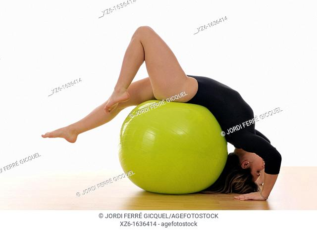 young woman doing exercise, gymnastics, with a large green ball, giant ball