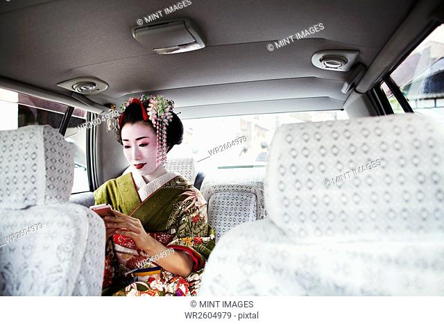A woman dressed in the traditional geisha style, wearing a kimono with an elaborate hairstyle and floral hair clips, with white face makeup with bright red lips...