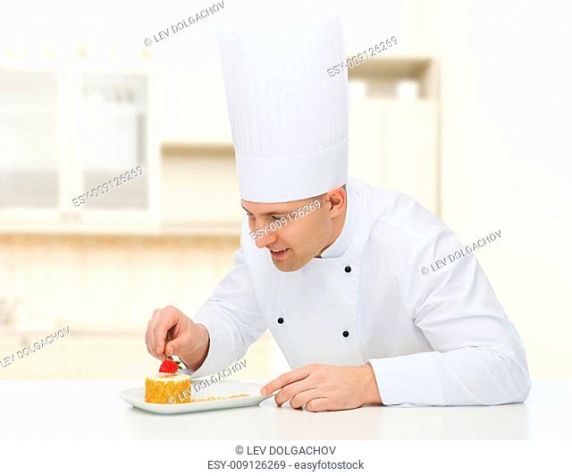 cooking, profession, haute cuisine, food and people concept - happy male chef cook decorating dessert over kitchen background