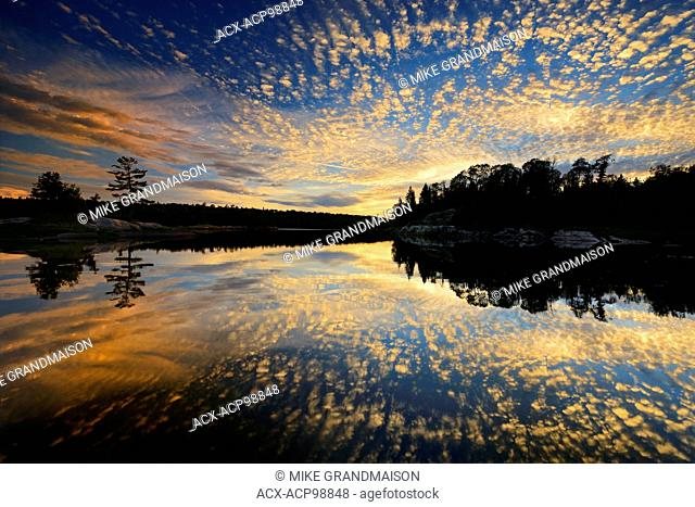 Clouds reflected in Middle Lake at sunset Kenora Ontario Canada