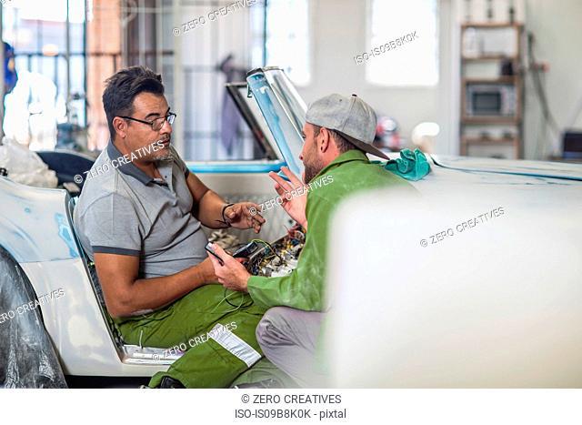 Colleagues chatting in bodywork repair shop