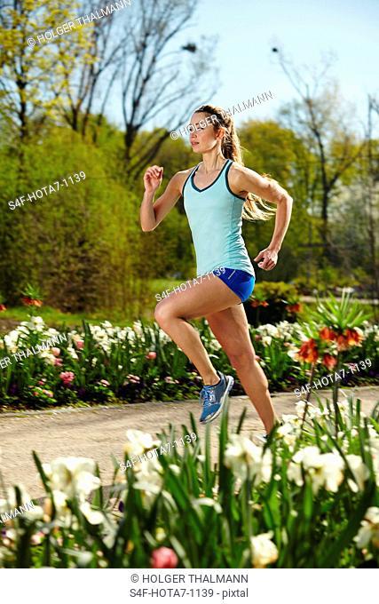 Sportliche Frau läuft in einem Park im Frühling