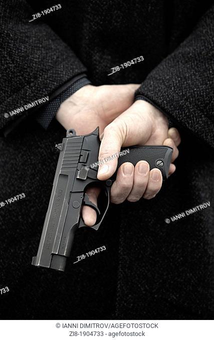 Man holding loaded gun behind his back
