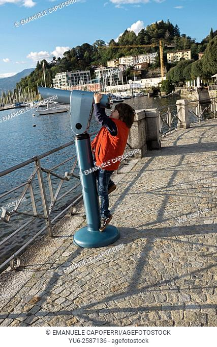 Child looks view through the telescope for tourists, Laveno, Italy