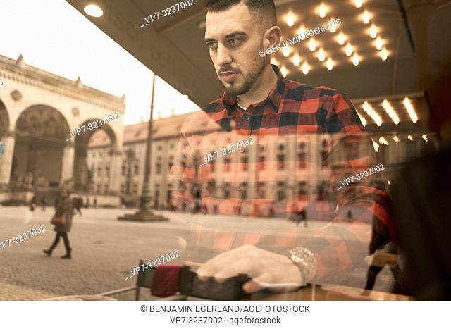man in café behind glass window reflecting Feldhernnhalle at Odeonsplatz Munich, city centre, working with laptop, self employee, freelancer, Greek ethnicity
