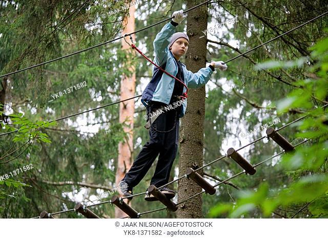 Teenage boy on exercise trail in adventure park trail, Otepää, Estonia