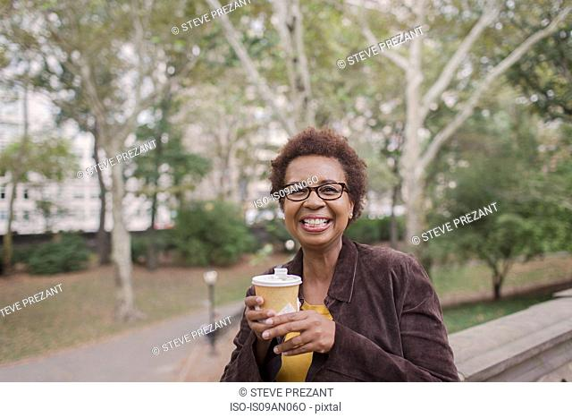 Portrait of smiling mature woman drinking takeaway coffee in park