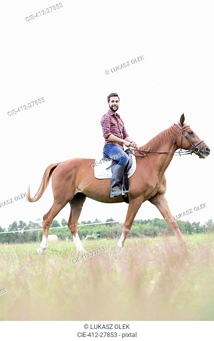 Portrait smiling man horseback riding in rural field