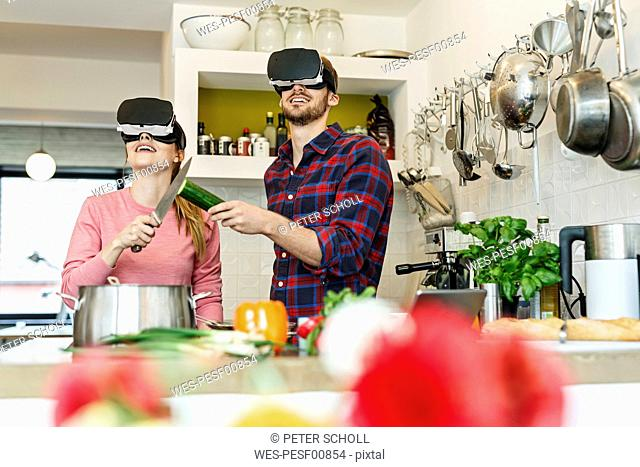 Happy young couple wearing VR glasses cooking together in kitchen