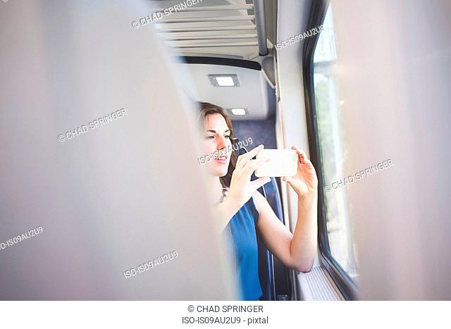 Mid adult woman on train, taking photograph through window using smartphone