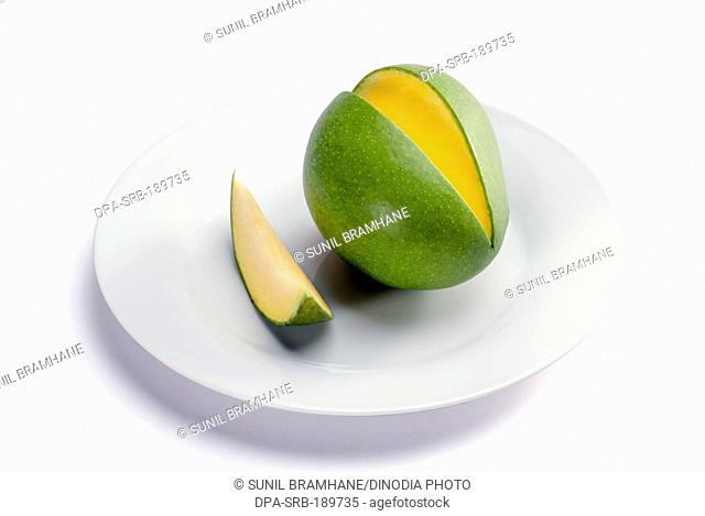 green Mango fruit with slice in plate on white background India Asia