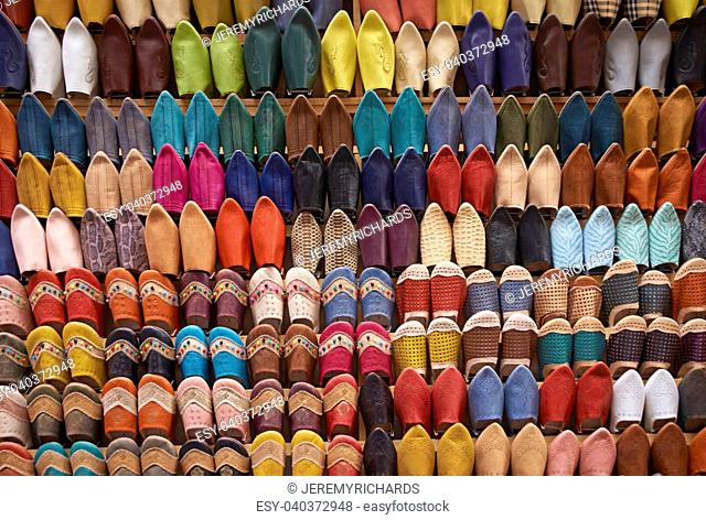 Colorful display of traditional leather slippers for sale in the souk of Fes in Morocco