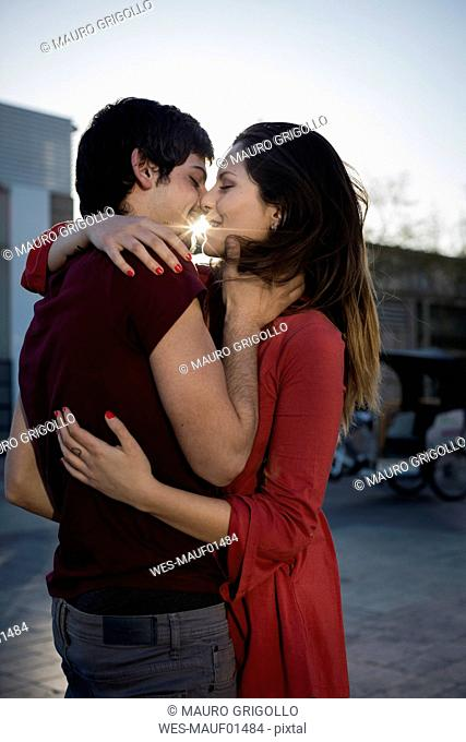 Affectionate young couple hugging and kissing on city square at sunset