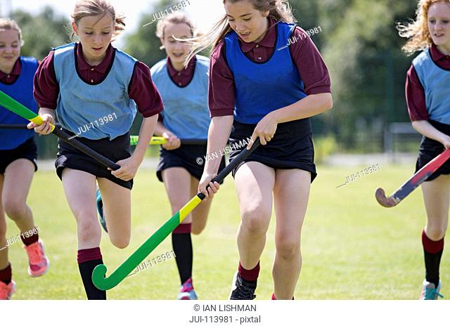 Middle schoolgirls playing field hockey on field in physical education class