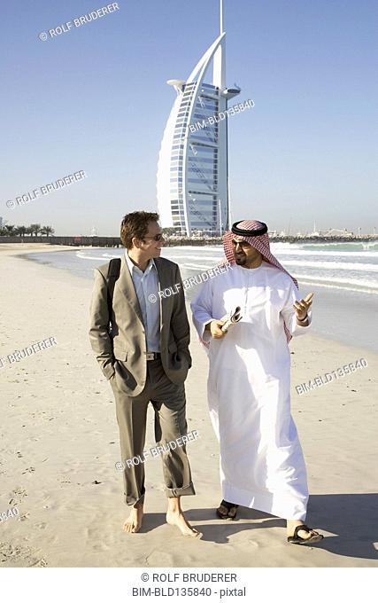 Businessmen walking on beach, Dubai, United Arab Emirates