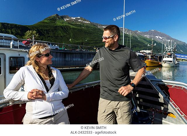 Couple talking while on the deck of their boat, Valdez small boat harbor, Prince William Sound, Southcentral Alaska