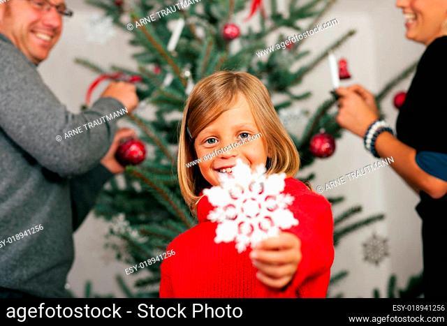 Familie schmückt den Weihnachtsbaum