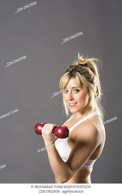 Beautiful blond woman exercising with weights smiling