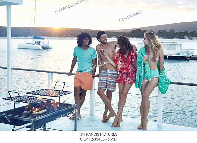 Young adult friends hanging out and drinking on summer houseboat